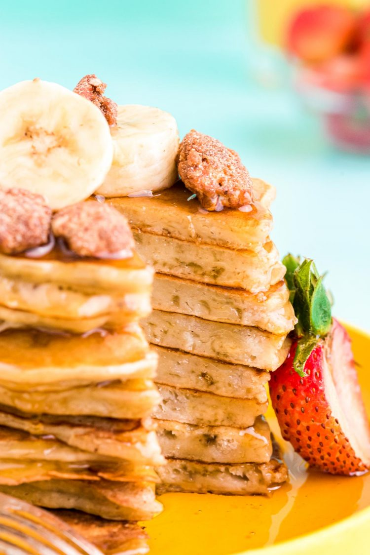 Close up photo of banana pancakes with a slice taken out of the stack.