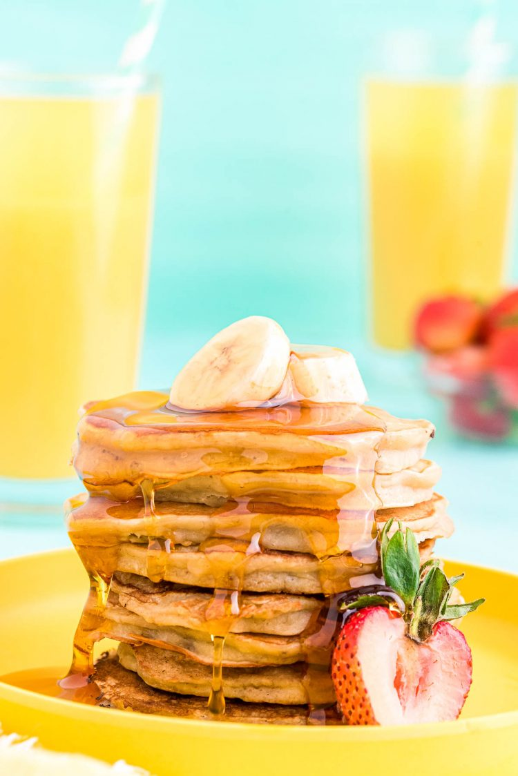 Close up photo of a stack of banana pancakes on a yellow plate topped with sliced banana and a strawberry on the side.