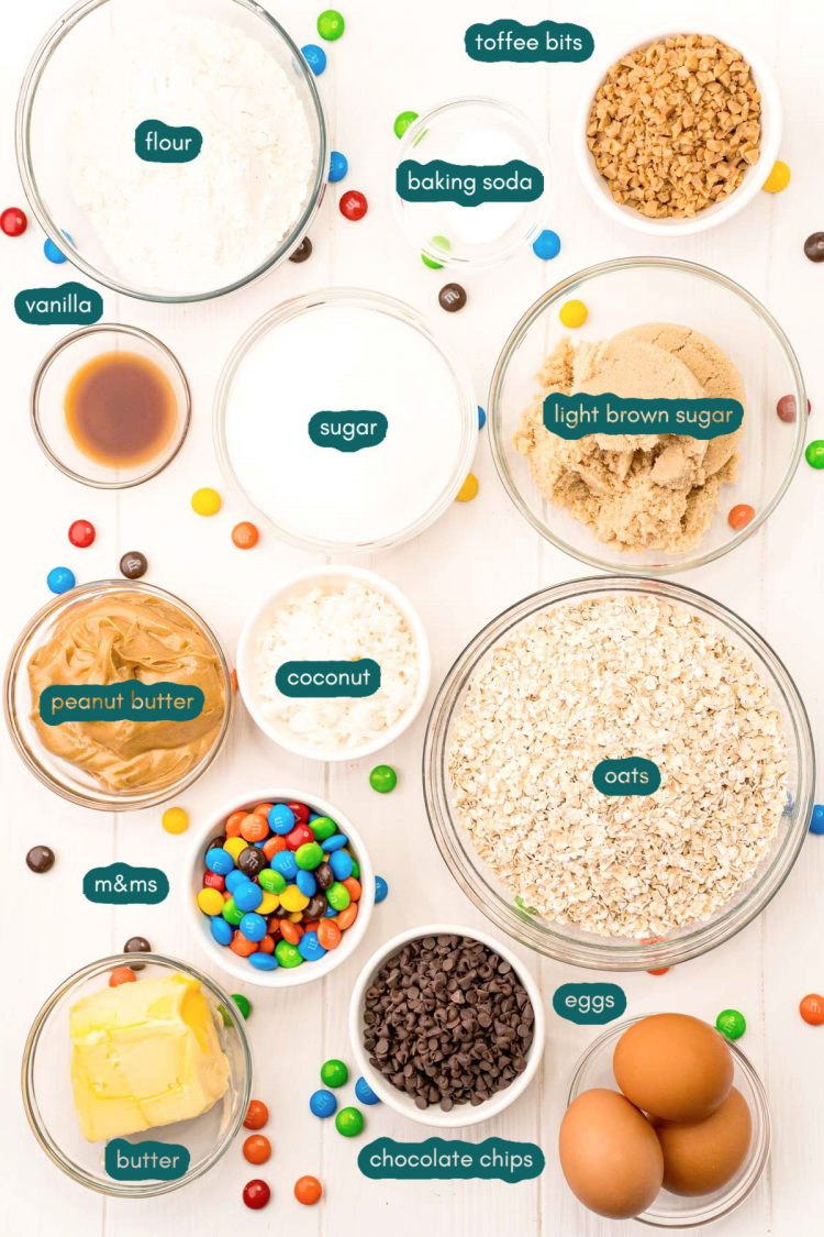 Ingredients to make monster cookies prepared on a white surface.