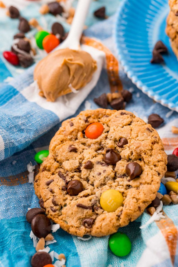 Monster Cookies on a blue napkin with M&Ms and chocolate chips scattered around.
