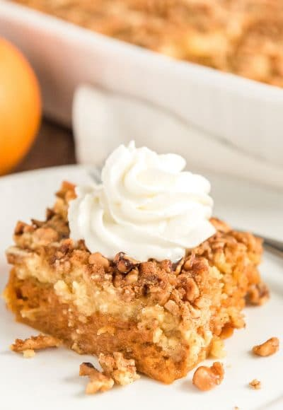 Close up photo of a slice of pumpkin dump cake on a white plate with pumpkin and more cake in background.