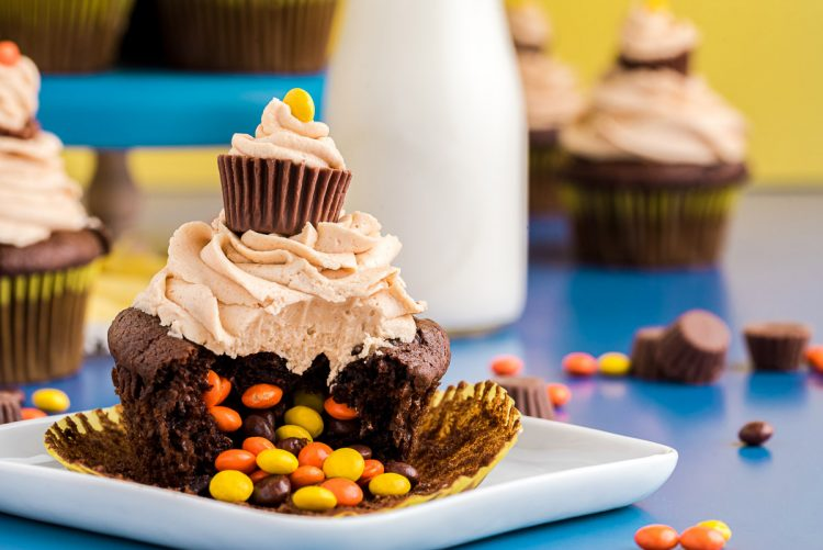 A chocolate cupcake with peanut butter frosting on a white plate with reese's pieces spilling out of the center where a bite has been taken.