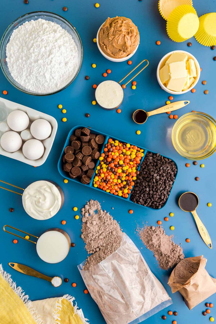 Overhead photo of ingredients prepped to make peanut butter chocolate cupcakes on a blue surface.