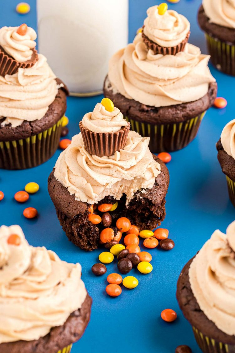 Close up photo of peanut butter chocolate cupcakes on a blue surface with a glass of milk and Reese's pieces scattered around.