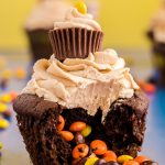 Close up photo of a peanut butter chocolate cupcake with mini Reese's pieces in the center falling out onto a blue surface.
