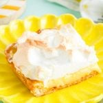 Close up photo of a slice of lemon meringue slab pie on a yellow plate on a blue surface.