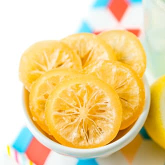 Sliced of candied lemons in a small white bowl.
