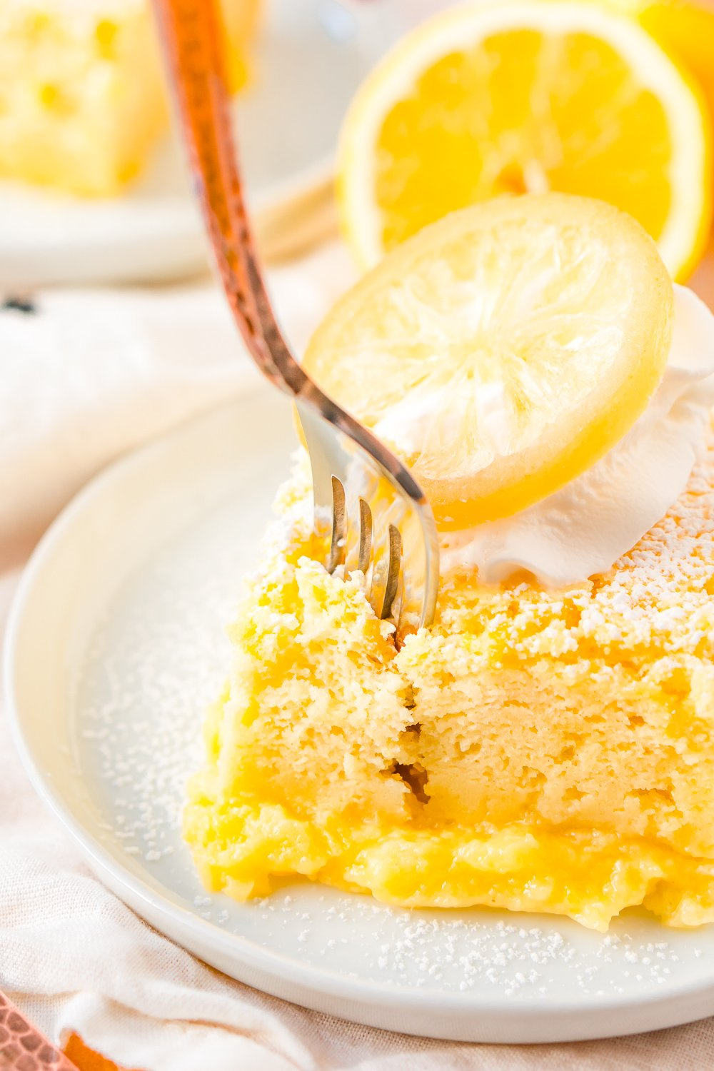 Fork digging into a slice of lemon cake on a small white plate.
