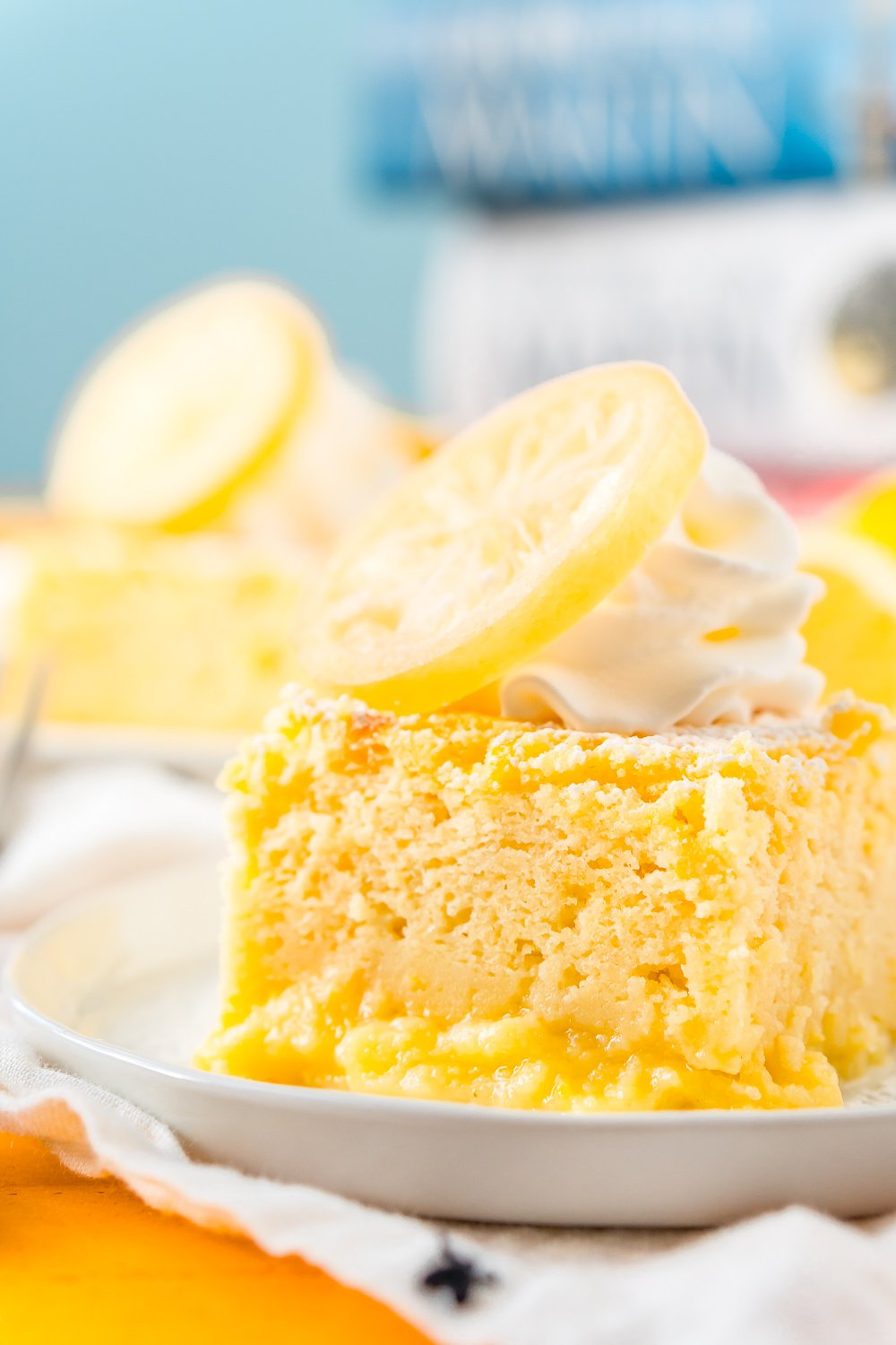 Close up photo of a slice of lemon cake on a small white plate.