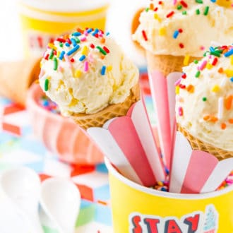 Three sugar cones with vanilla ice cream and sprinkles resting in a yellow bowl.