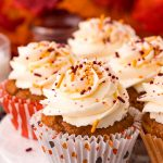 Close up photo of pumpkin cupcakes on a white cake stand with leaves in the background.