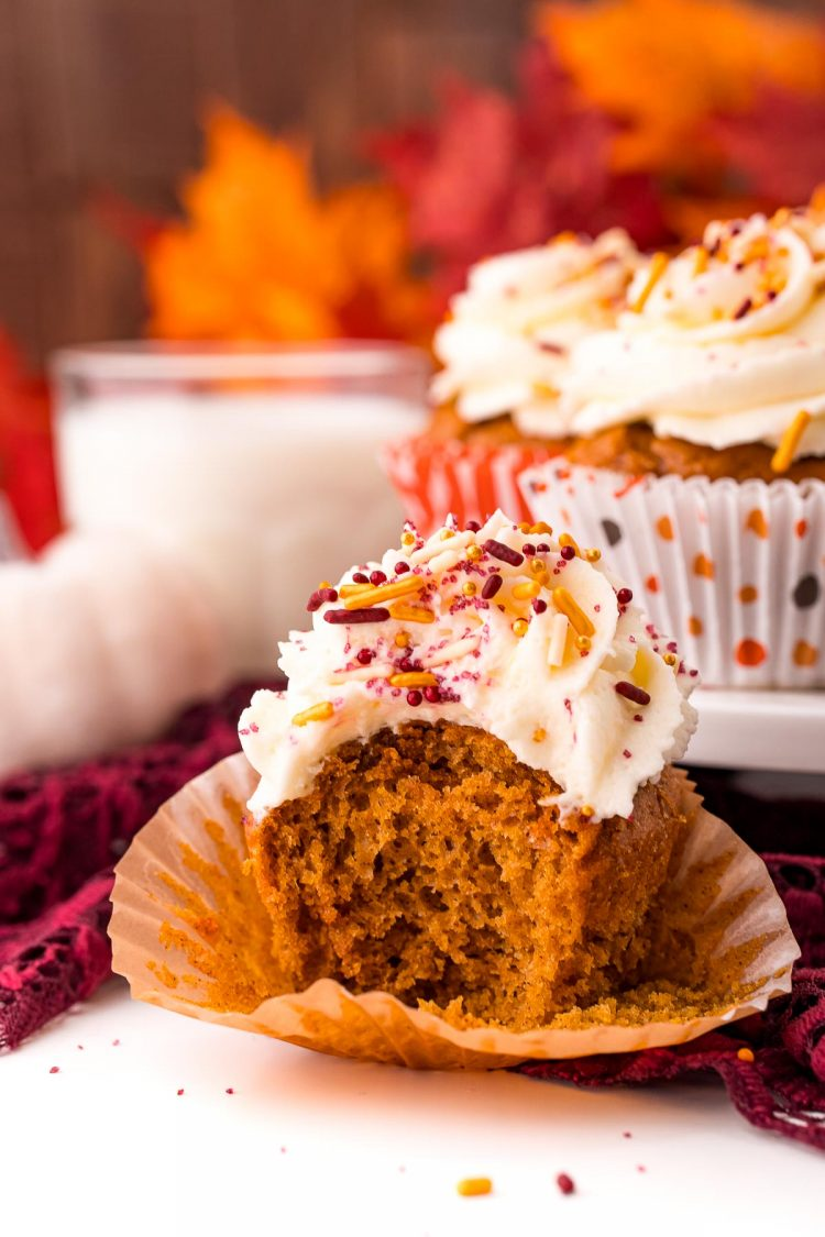 A pumpkin cupcake with a bite taken out of it on a white table with a cake stand with more cupcakes and a glass of milk in the background.