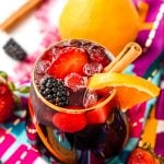 Glass filled with red sangria garnished with a cinnamon stick and and orange slice.