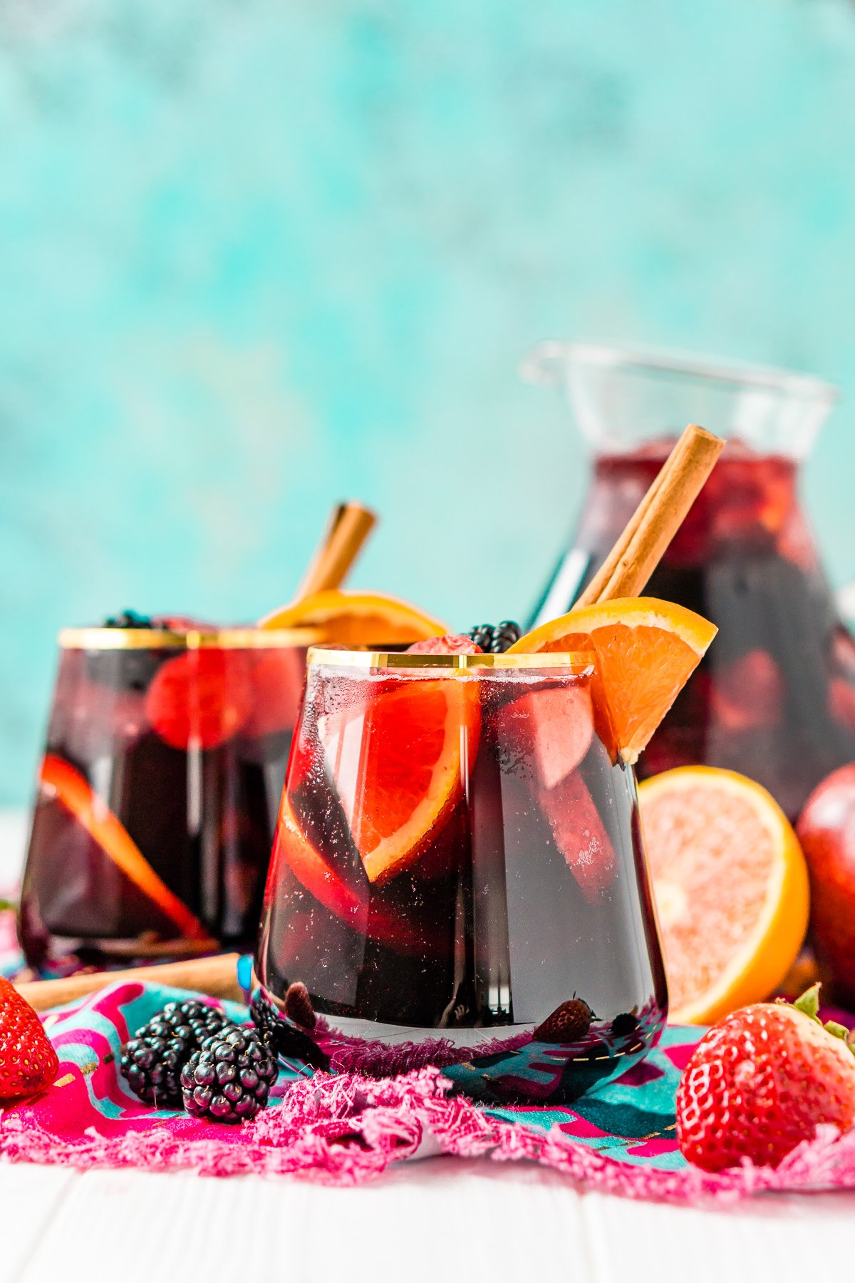 Glasses of red wine sangria in front of a full pitcher. Fresh fruit scattered around glasses.