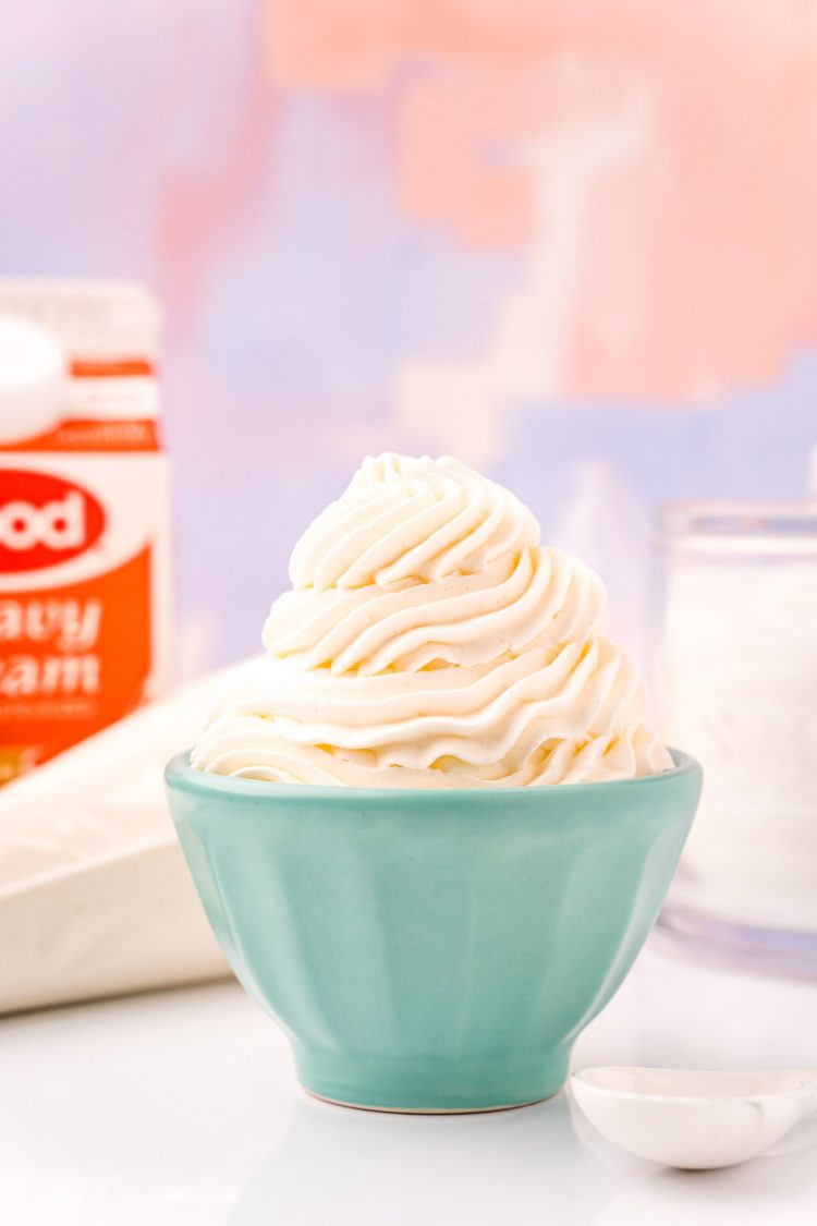 A small light blue bowl filled with piped whipped cream with a bag of whipped cream and a carton of heavy cream in the background.