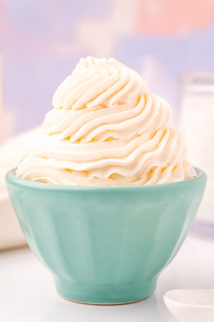 Close up photo of a light blue bowl that has whipped cream piped into it.