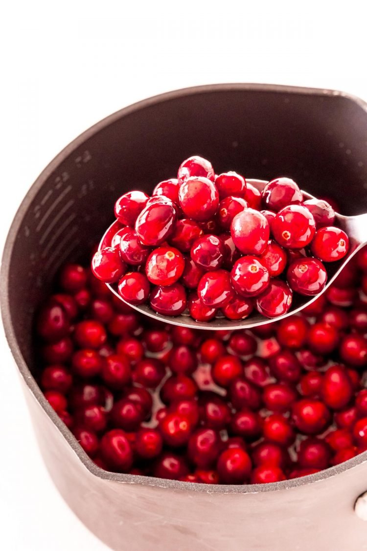 A spoon lifting cranberries out of a pot.
