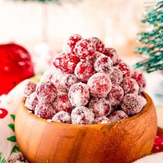 Close up photo of sugared cranberries in a wooden bowl surrounded by holiday decorations.