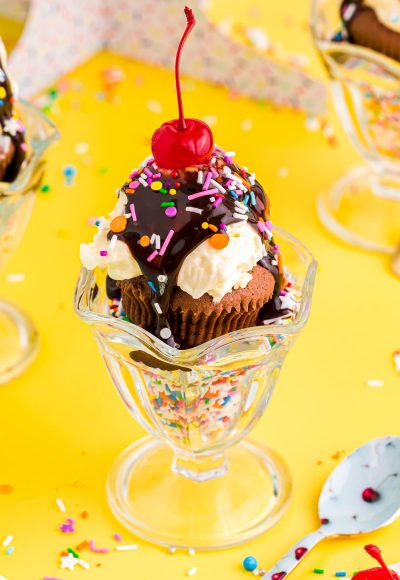 Close up photo of brownie cupcakes in a sundae dish filled with sprinkles on a yellow table.
