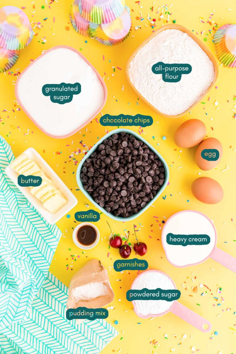 overhead photo of ingredients to make brownie cupcakes on a yellow surface with a teal napkin and rainbow sprinkles scattered around.