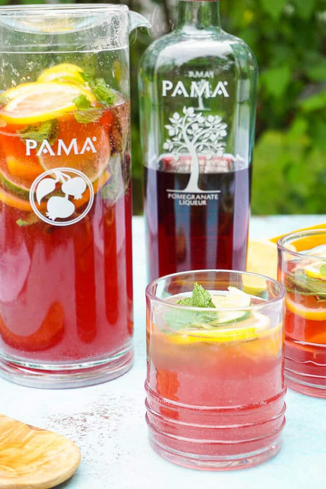 Celebrate summer with this Pomegranate Citrus Rum Punch! Sweet PAMA Pomegranate Liqueur paired with lemonade, lemon lime soda, and rum for a splash of summer fun. Plus a recipe video!