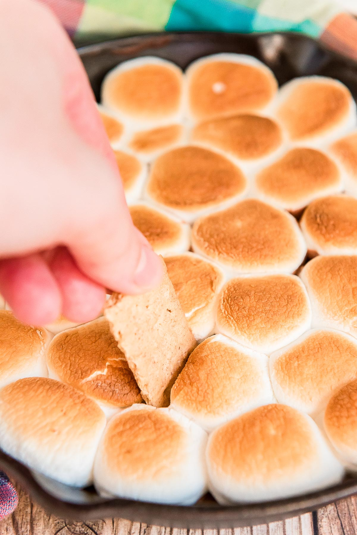 Woman's hand scooping a graham cracker piece into a cast iron skillet filled with toasted marshmallows.