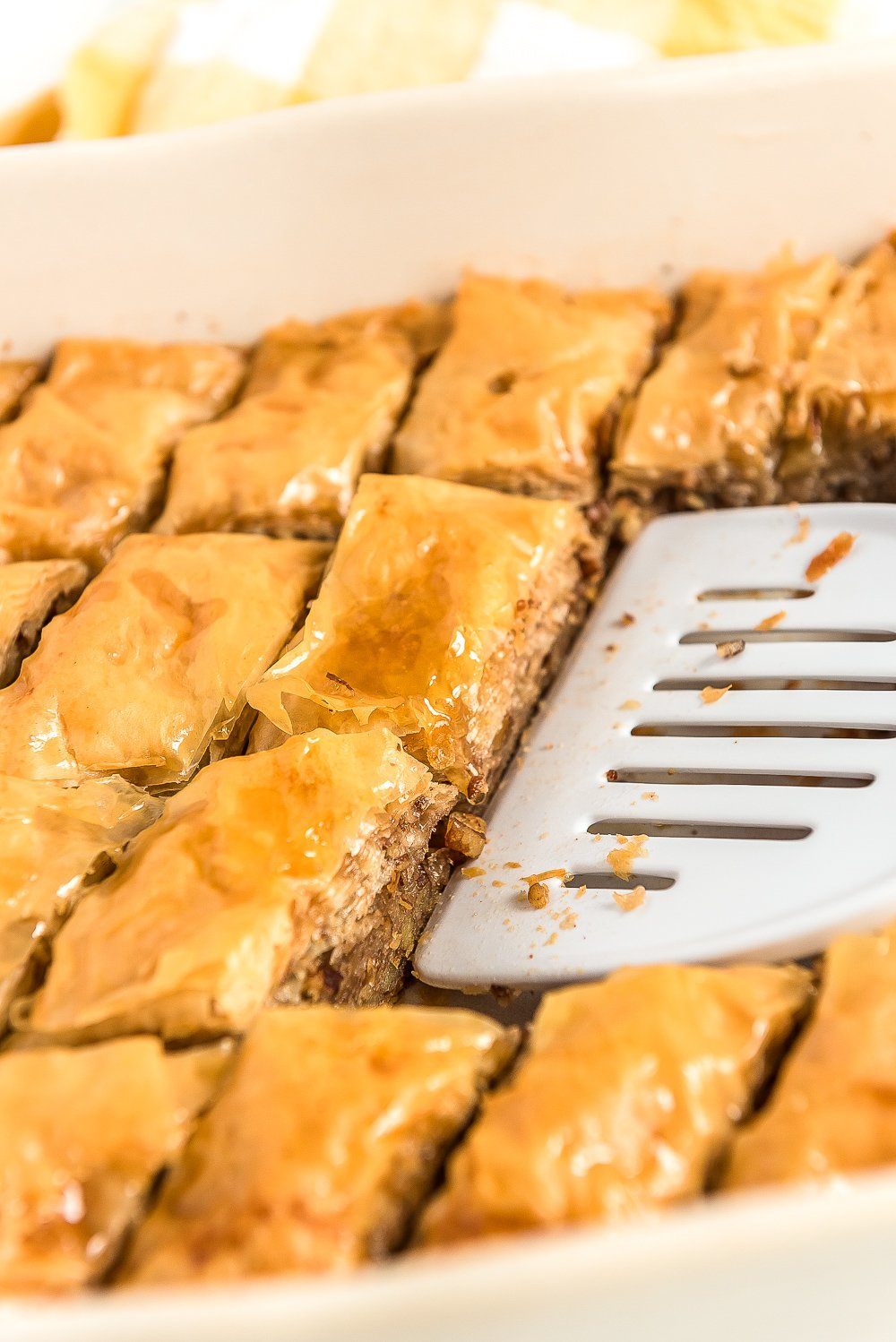 Spatula scooping pieces of baklava out of a baking dish.