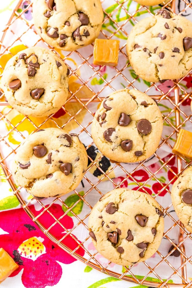 Overhead photo of chocolate chip cookies with caramel on a cooling rack.
