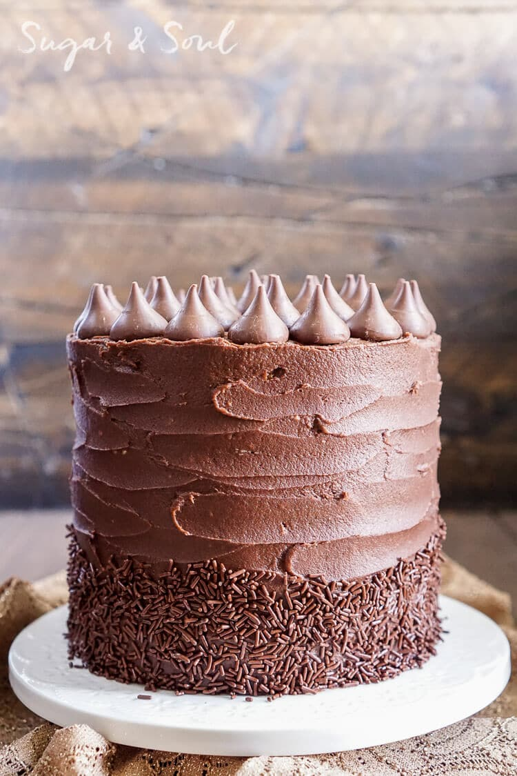 This Pumpkin Chocolate Kisses Cake is the ultimate pumpkin and chocolate combo for fall! Five layers of sweet and fluffy pumpkin cake wrapped in a whipped chocolate buttercream frosting!