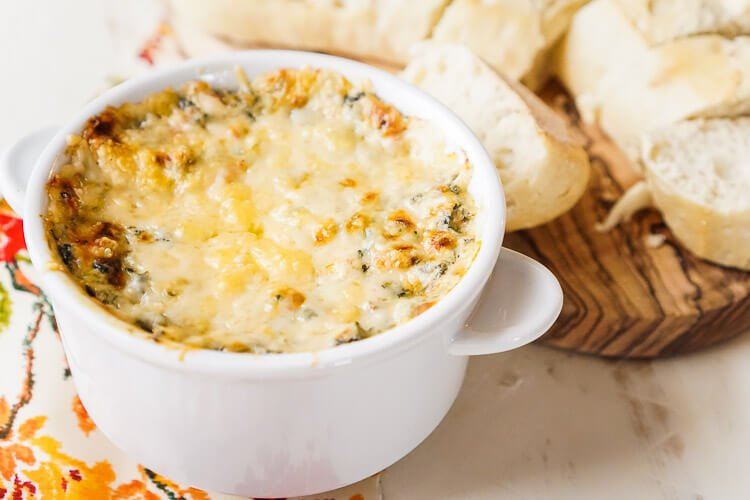 This Baked Spicy Spinach Dip is the appetizer we all know and love with a little added kick! A creamy and hearty appetizer with a hint of cayenne and cherry peppers make this a serious crowd-pleaser!