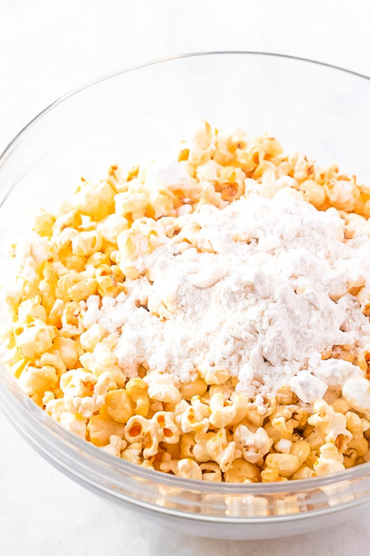 popcorn and dry cake mix in a a glass mixing bowl.