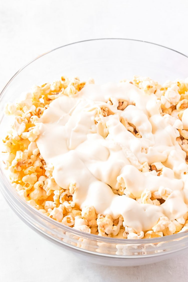 Melted white chocolate on top of popcorn in a mixing bowl.