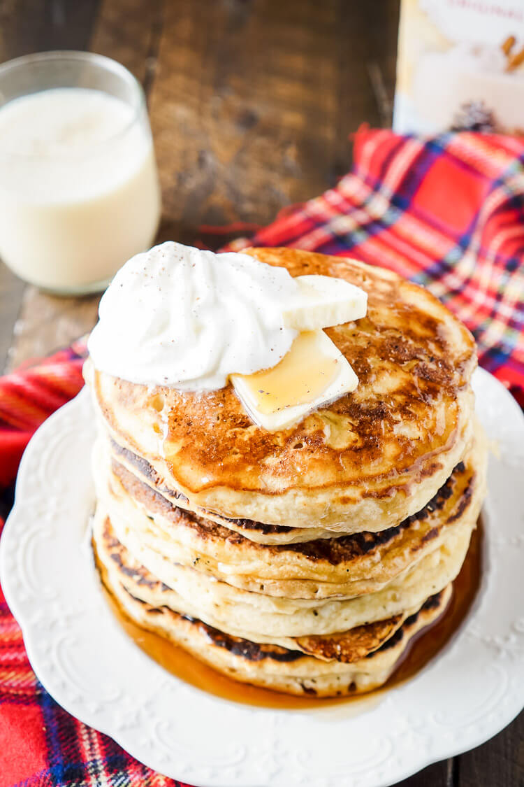 These Eggnog Ricotta Pancakes are fluffy and full of holiday flavor! Made with a creamy eggnog and ricotta base, these cook right up in minutes and make a fantastic holiday breakfast! Top them with butter, syrup, and whipped cream!