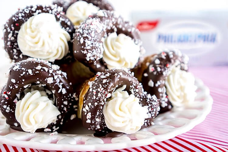 These Chocolate Peppermint Cheesecake Cream Horns are a simple dessert with a flaky pastry that's been dipped in chocolate, sprinkled with peppermint candy pieces, and finished with a peppermint cream cheese filling.