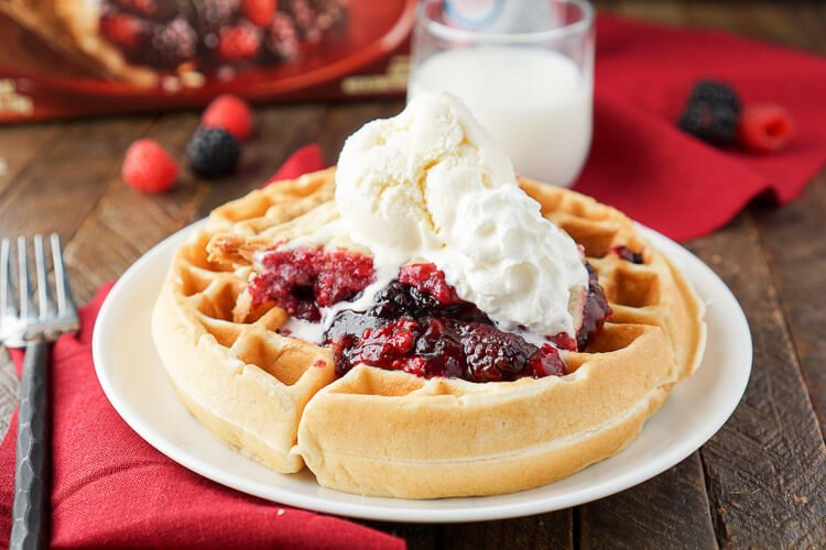 These Pie à la Mode Belgian Waffles are the ultimate post-holiday breakfast. Made with large and fluffy Belgian Waffles and topped with a slice of warm pie, ice cream, and whipped cream - they're the ultimate breakfast and dessert mashup! A great way to use leftover pie from the holidays!