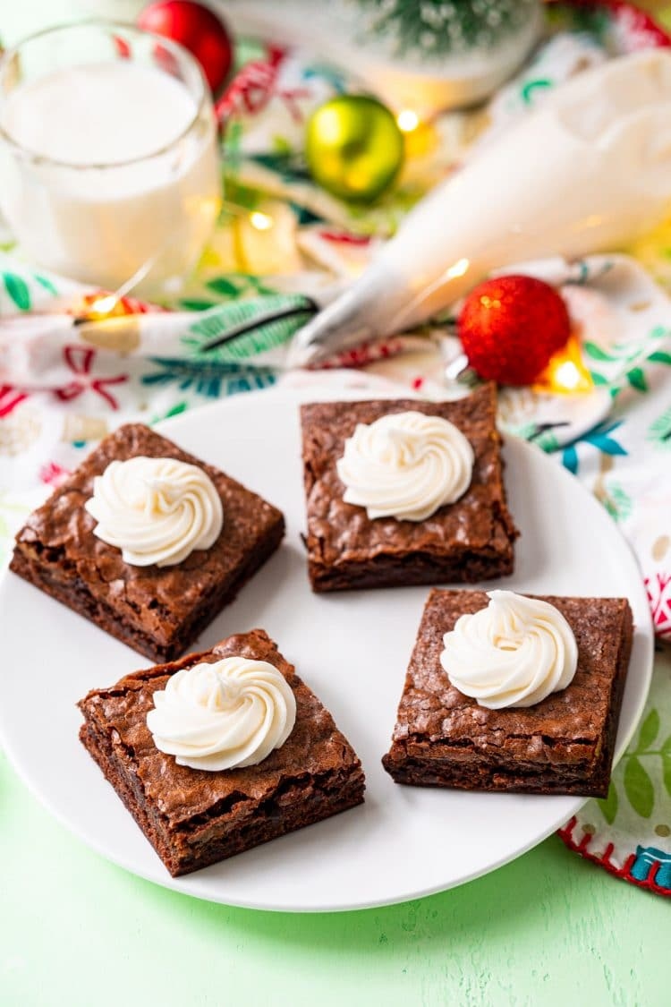 Brownies on a white plate with swirls of buttercream frosting on them and holiday decorations scattered around.