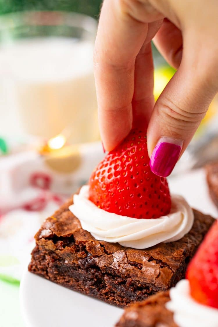 A woman's hand placing a strawberry on top of a frosted brownie.