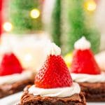 Close up photo of square brownies decorated with frosting and strawberries to look like santa hats.
