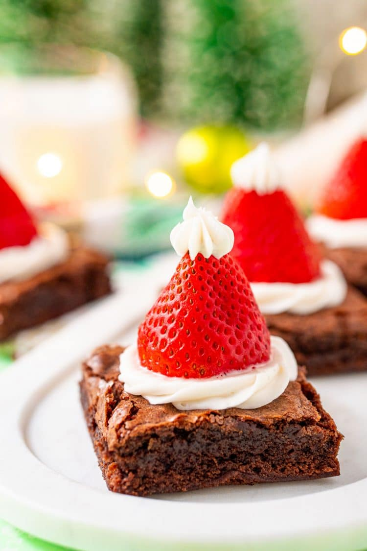 Close up photo of a serving tray with santa hat decorated brownies on it for a holiday party.