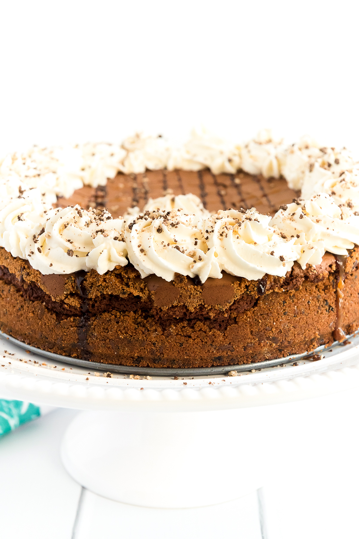 Brownie pie on a cake stand topped with chocolate and caramel drizzle and whipped cream.