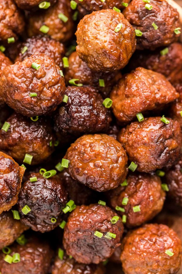 Close up photo of meatballs garnished with chives.