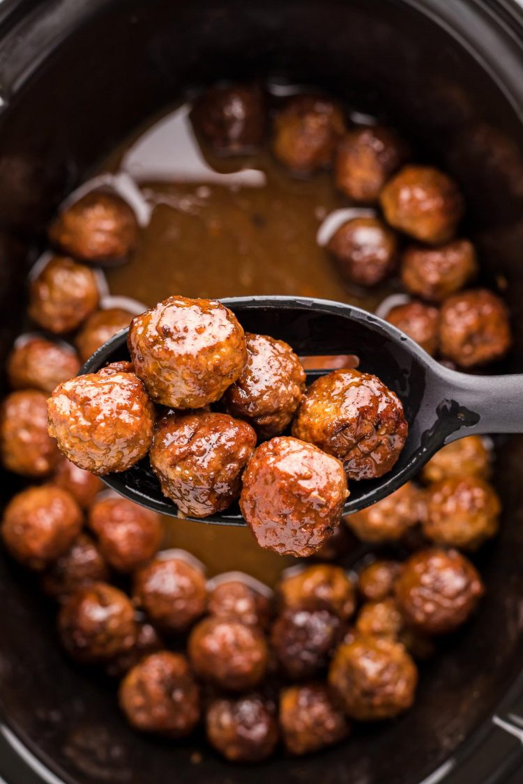 Close up photo of a serving spoon scooping merlot meatballs out of a crockpot and towards the camera.
