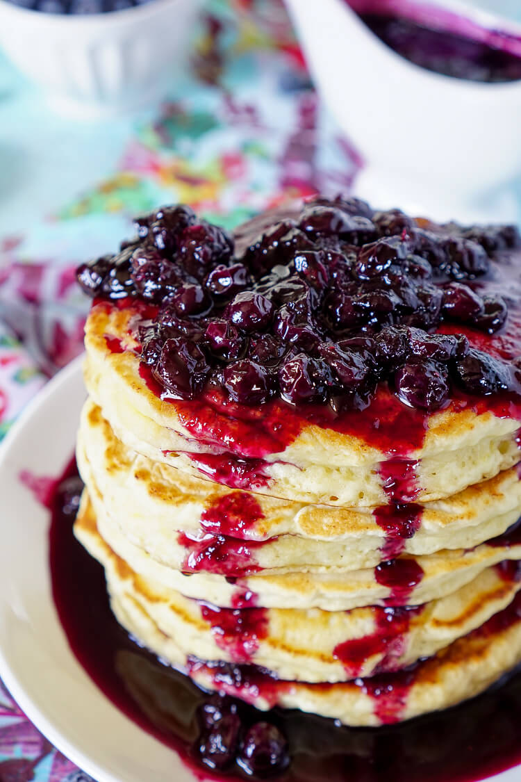 These Lemon Ricotta Pancakes are fluffy and laced with zest, then topped with a homemade Blueberry Honey Syrup for a sweet finish!