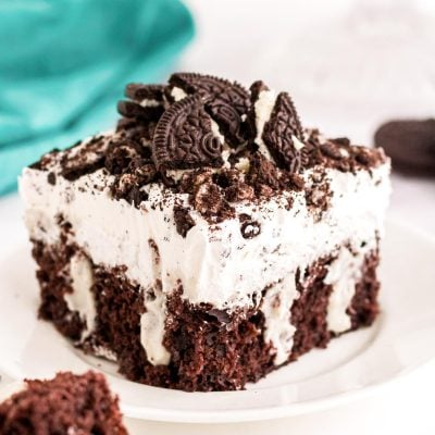 Close up photo of a piece of Oreo poke cake sitting on a white plate.