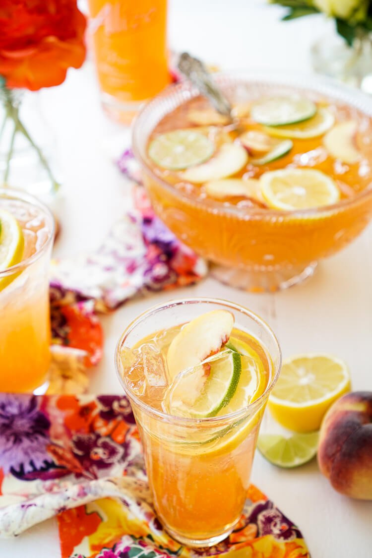 This Spiked Peach Punch is the perfect big batch cocktail for summer! Smooth Alizé Peach vodka blends with white rum, lime juice, and ginger ale for a refreshing and vibrant warm weather beverage!