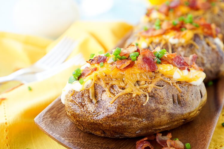 These are the Best Ever Baked Potatoes, they're perfectly seasoned and loaded up with a creamy dressing, cheddar cheese, bacon, and chives!
