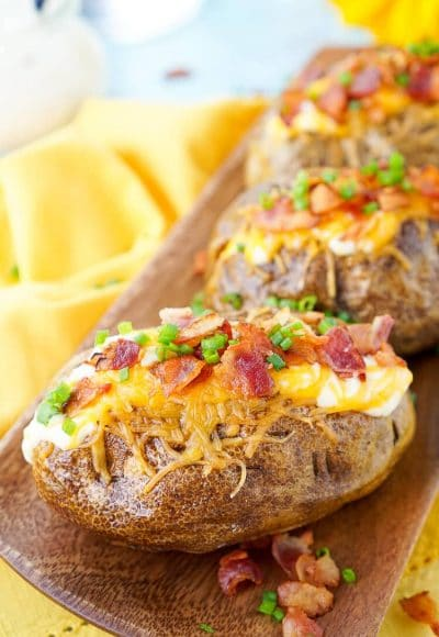 These are the Best Ever Baked Potatoes, from the prep work to the toppings, they're perfectly seasoned and loaded up with a creamy dressing, cheddar cheese, bacon, and chives!