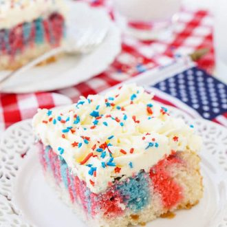 This Red, White, and Blue Marble Sheet Cake is made with an adapted cake box mix and topped with a whipped white chocolate frosting. It's the perfect patriotic dessert for the 4th of July!