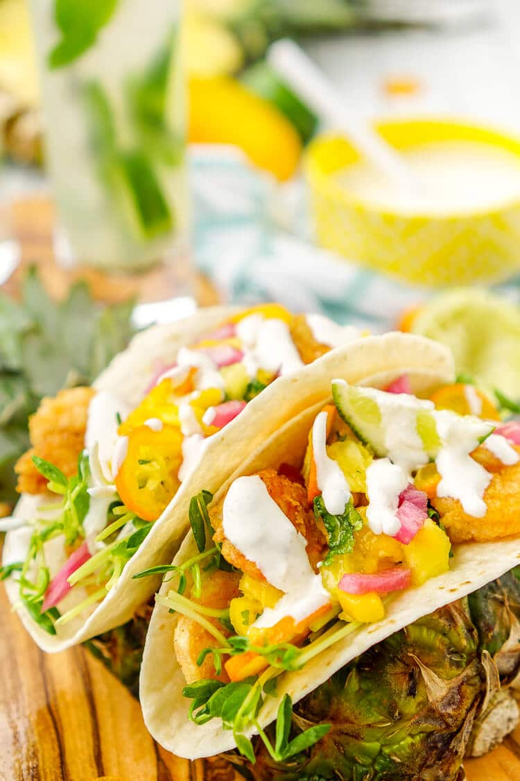 These Tropical Shrimp Tacos are a fruity twist on the classic Mexican dish and loaded up with vibrant flavors and a splash of tequila! Lightly breaded shrimp is topped with a pineapple, mango, and mint salsa, with the addition of pea shoots, kumquats, and pickled onions. Finally it's finish off with a tequila lime dressing.