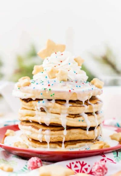 These Sugar Cookie Pancakes will add holiday cheer to your morning routine. Trade in traditional buttermilk for thick, fluffy, and sweet ricotta based pancakes laced with sugar cookie creamer, and topped with baked sugar cookies, icing, whipped cream, and sprinkles!